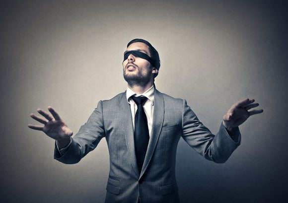 Blindfolded man in gray suit feeling his way around a room