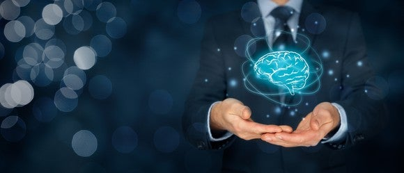 Businessman in suit holding electronic brain representing artificial intelligence.