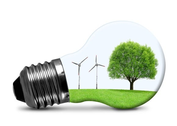 A light bulb with wind turbines and a tree inside.