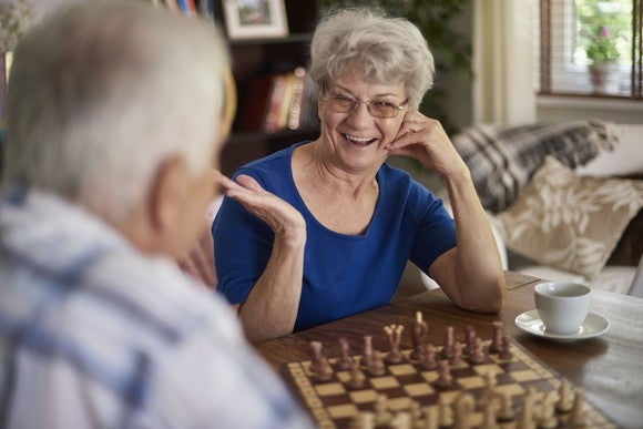 Retired couple playing chess.