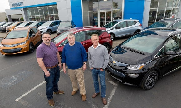 The three owners with their Bolts in front of a Chevrolet dealership.