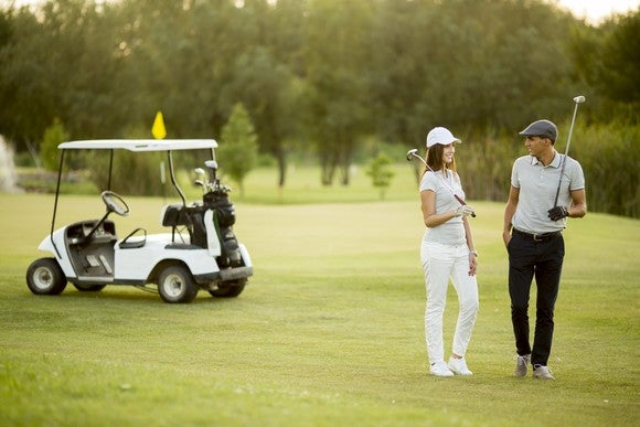 Woman and man playing golf.