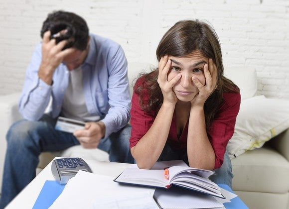 Frustrated younger couple looking at a credit card and at bills