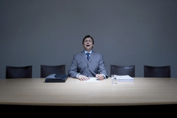 Businessman working alone in boardroom, crying, portrait