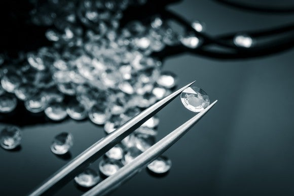Examining a diamond in a pair of tweezers.