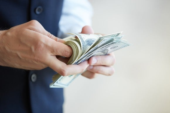 A businessman counting money with his hands.