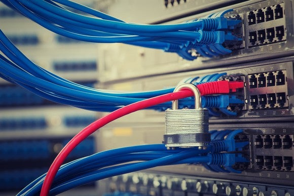 Network switch with several blue Ethernet cables attached, plus one red cable connected through a standard padlock.