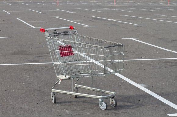 An empty shopping cart sitting in an empty parking lot.