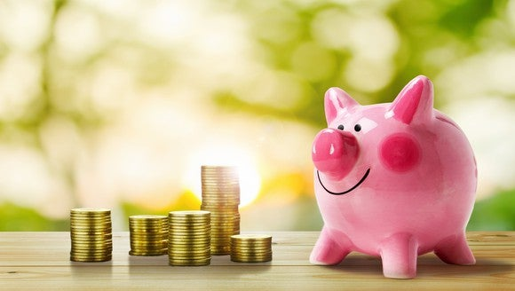 Stacks of gold coins next to a smiling piggy bank.