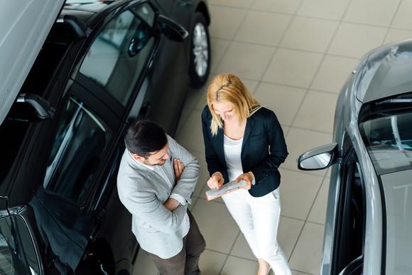 A man talks with a car salesman.