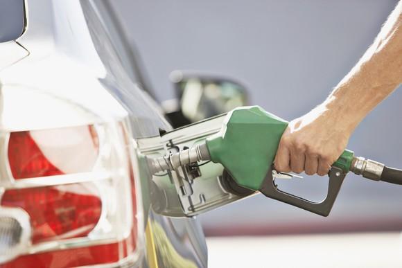 A person pumps gas.