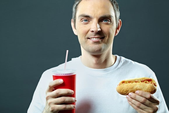 A man holds a hot dog and a soda