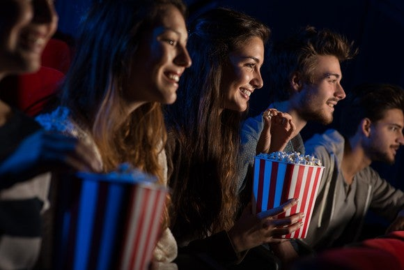People sitting in a movie theater, smiling and eating popcorn.