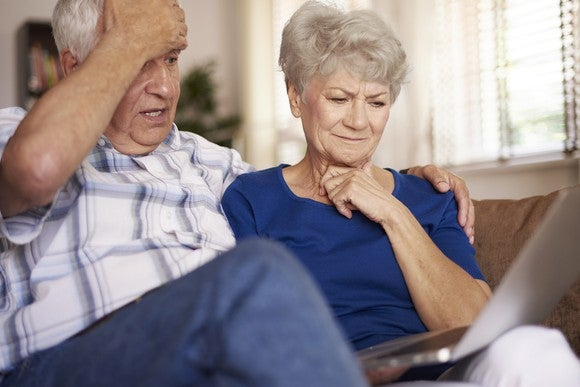 Older couple with worried expressions looking at computer screen.
