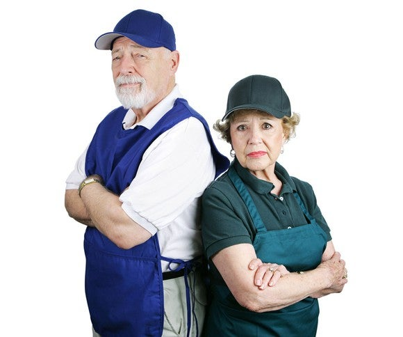 Older couple dressed in work clothes with sad expressions.