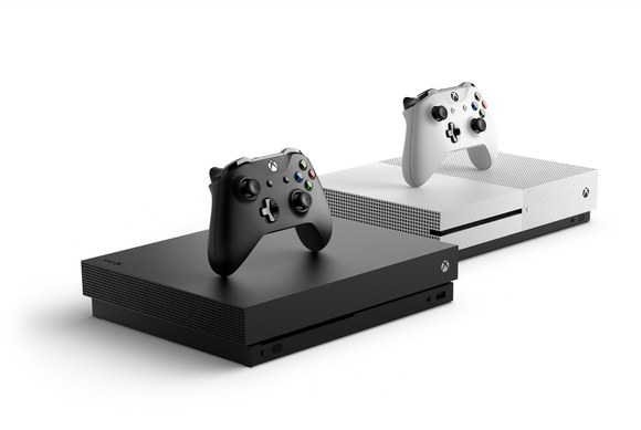 Two Xbox One X consoles, one white and one black, side by side against white background.