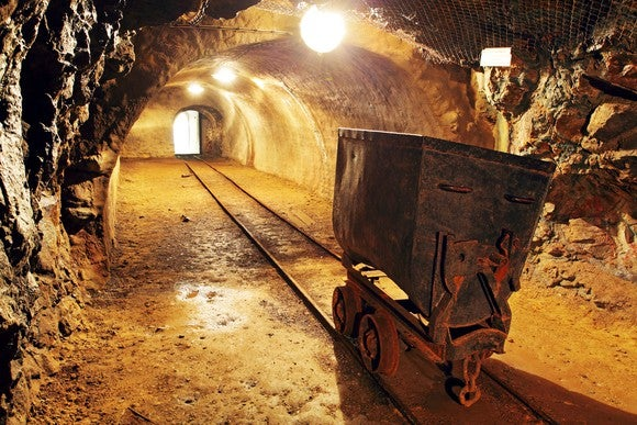 A car on tracks inside a gold mine.