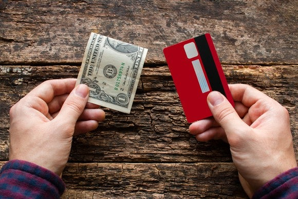 A person holds a folded dollar bill in one hand and a credit card in the other.