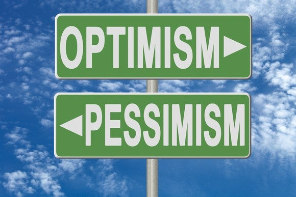 "Green signs that say ""optimism"" and ""pessimism."""