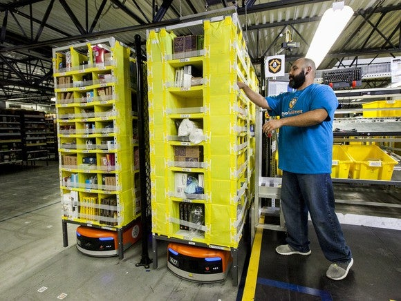 Amazon worker picking items from a bin.