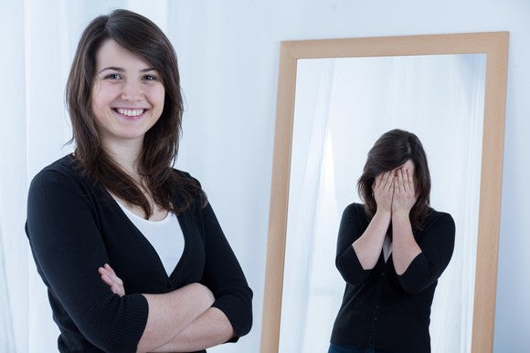 A woman looks confident, but in the mirror, she has her hands over her face.