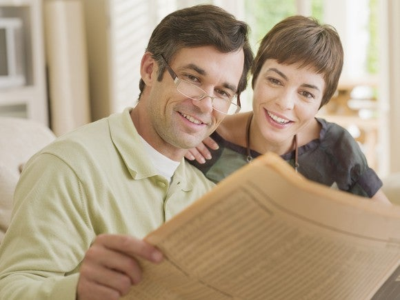 A husband and wife looking at a financial newspaper.