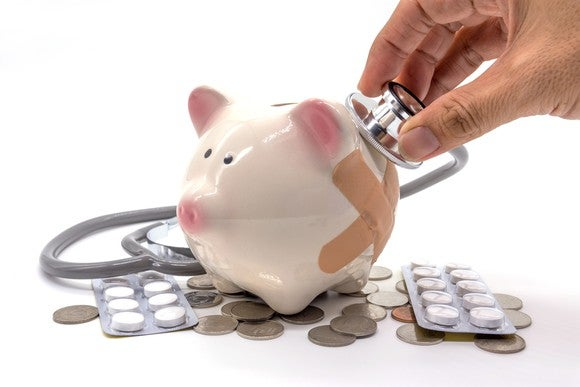 A person holds a stethoscope up to a piggy bank wearing band-aids.