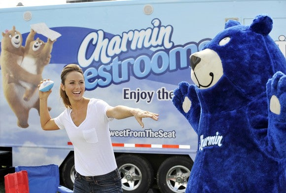 A person in a blue bear suit and a woman preparing to throw a ball both stand in front of a Charmin truck, in a marketing event.