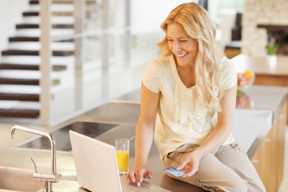 A lady shops online, suggestive of the kind of growing e-commerce platforms operated by Mercadolibre and Alibaba.