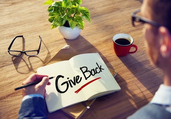 "A person writing the words ""give back"" in a book."