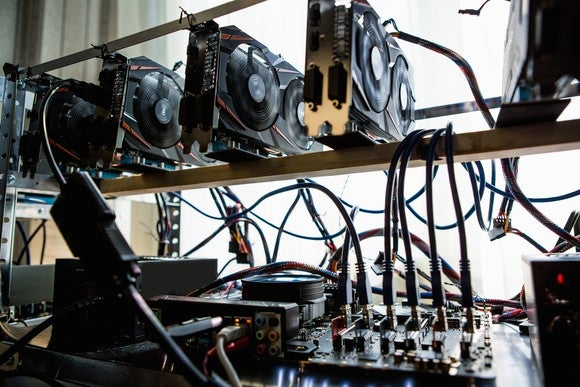 A computer with multiple hard drives and graphic cards operating by a cryptocurrency miner.