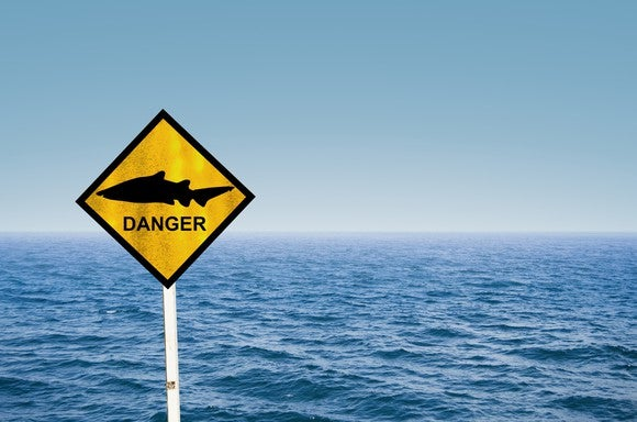 A sign with a picture of a shark and the word danger.