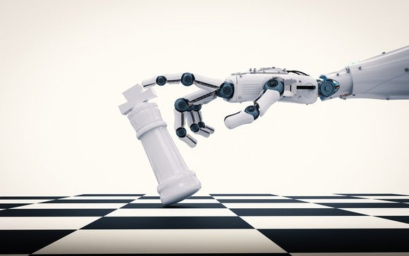 A robot arm tips over a king on a chess board.