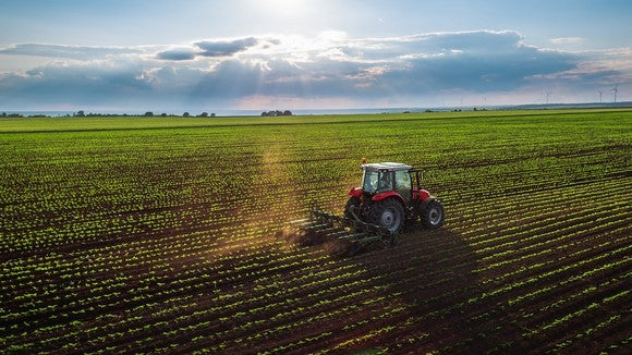 Tractor on a farm in field of crops.