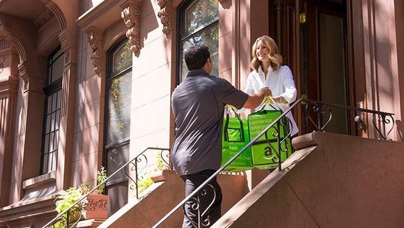 A man delivering two bags of groceries to a woman on her stoop.