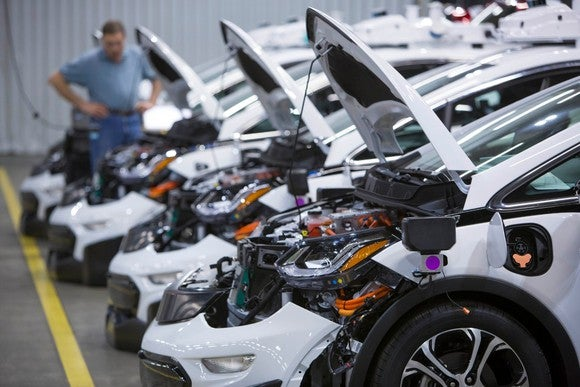 A lineup of driverless General Motors' Chevy Bolts sits inside a factory.