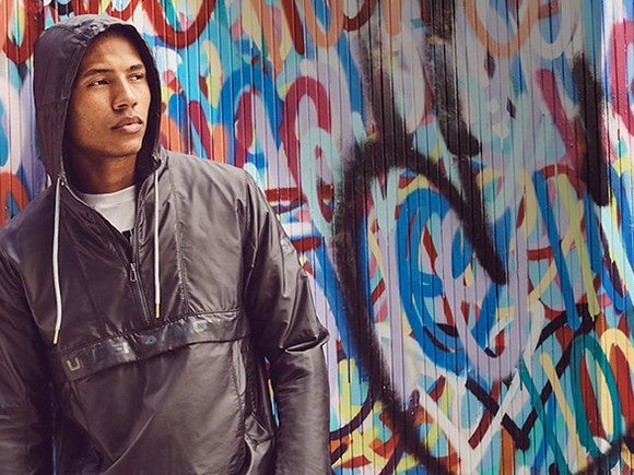 A model sporting an Under Armour windbreaker against a graffitied background.