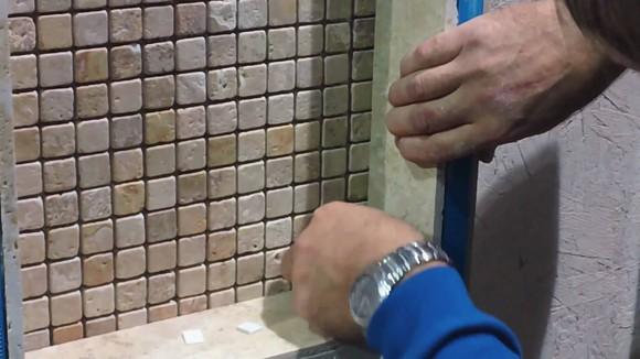 Tile installer working in bathroom.
