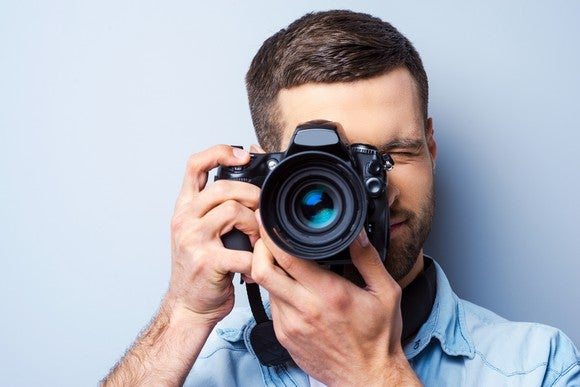 Man facing viewer with camera, about to take photo.