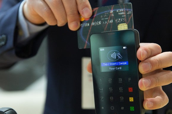 Man in suit swiping credit card through payment terminal.