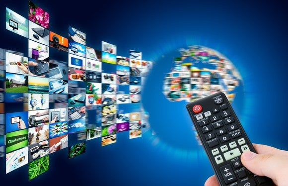 A person holding a television remote pointed at a variety of channels around the world.