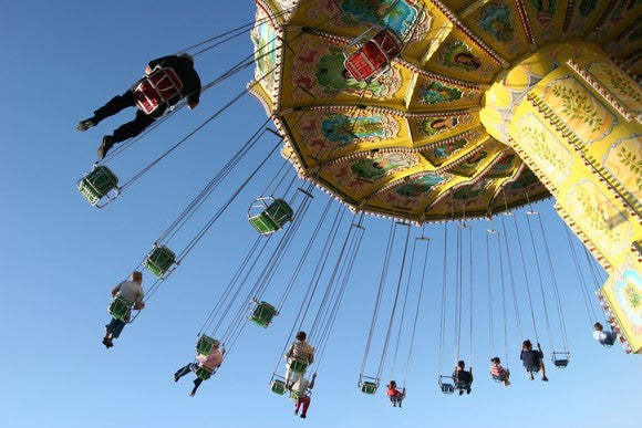 People riding on carousel swing high in air.