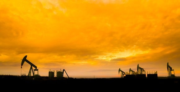 Silhouette of oil pumps at oil field with sunset sky background.
