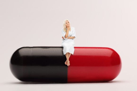 A woman contemplates a decision while sitting on a giant two-tone medicine capsule.