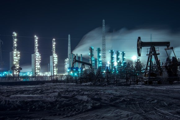 Oil pumps and an industrial site at night.