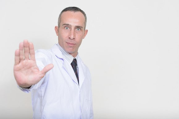 A doctor with an outstretched arm, as if signaling someone to stop.