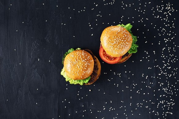 Two burgers on a black table
