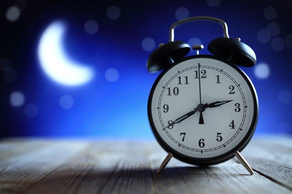 An alarm clock with the moon and stars in the background.