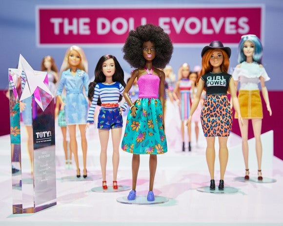"A lineup of diverse dolls standing in front of a banner reading ""The Doll Evolves"" with the Doll of the Year Award."