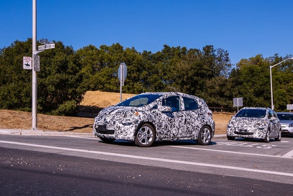 Two Chevrolet Bolt EVs in camouflage are shown testing on public roads in Palo Alto, California, near Tesla's headquarters.